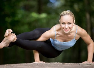 Weight Loss & Toning - A picture of a fit young woman practicing yoga outdoors in park.